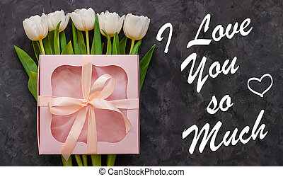 White tulip flowers and pink gift box on dark background ...