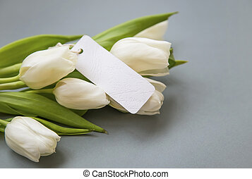 White tulips bouquet with blank label card , women's day greeting card copy space