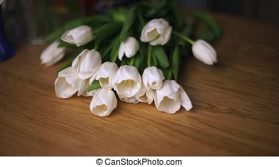 White tulips lie on the table.