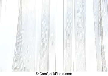 White tulle curtain with vertical folds. Window with light curtains. Soft textile texture. Light and shadow abstract background.
