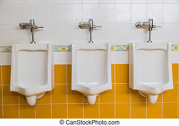 white urinals in men's restroom