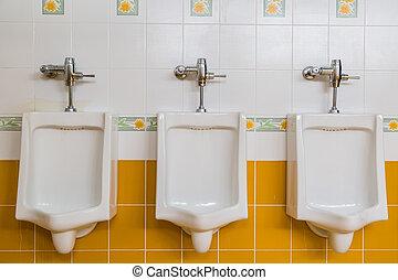 white urinals in men's restroom