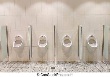 White urinals in the men's room. On the wall, front view.