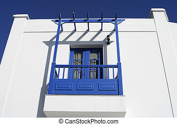 white villa with blue balcony
