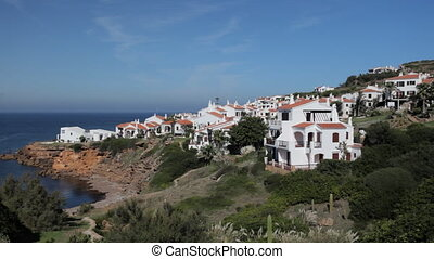white villas in the cliffs overlooking the sea, menorca, spain