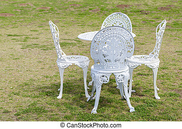 White vintage chairs on grass