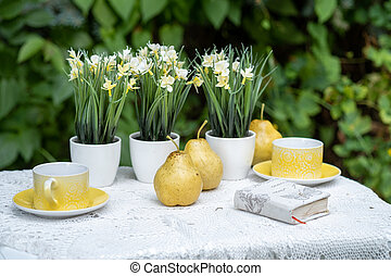 Coffee table with teacups and pears, book and flowers in garden