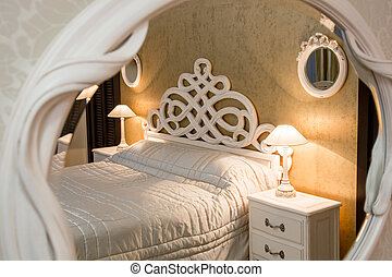 White vintage style carved bed and nightstand with lamps sen through the carved mirror