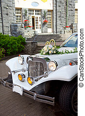 White vintage wedding car decorated with rings, bells and ...