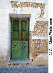 White wall with texture, green wooden door