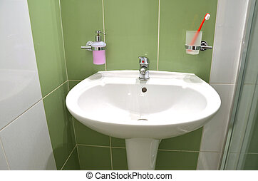 White wash basin, soap container and toothbrush in glass in...