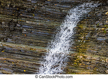 White water stream waterfall along the ribbed wet mountain wall