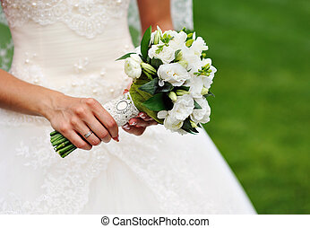 white wedding bouquet in hands of the bride