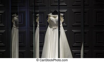 White wedding bridal dress on dark wall with reflections in mirrors
