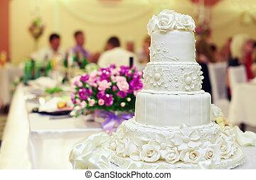 white wedding cake on restaurant interior background