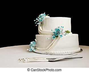 white wedding cake with blue flowers on a table with a black...