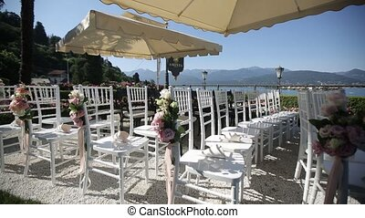 White wedding chairs in an open ceremony with flowers and ornaments in Italy