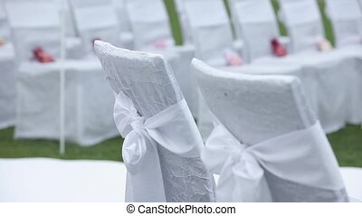 White wedding chairs in an open ceremony with flowers and ornaments