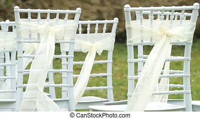 White wedding chairs with silk ribbons