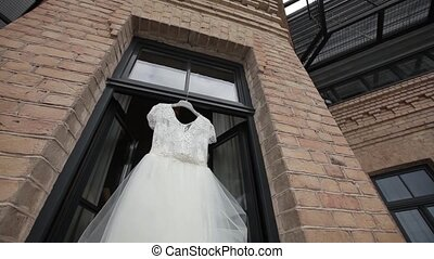 White wedding dress hanging in the aperture windows on the...