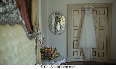 White wedding dress hanging in the doorway in the castle the day before the ceremony