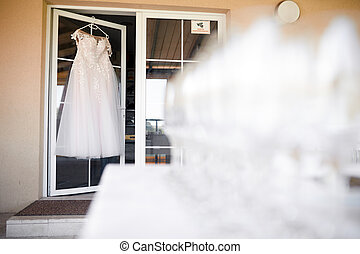 white wedding dress hanging on a hanger on a white door