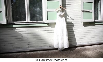 White wedding dress hanging on a white wooden house background against a white wall the day before the ceremony