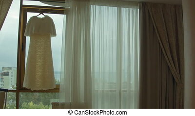 white wedding dress hangs in the window before the ceremony