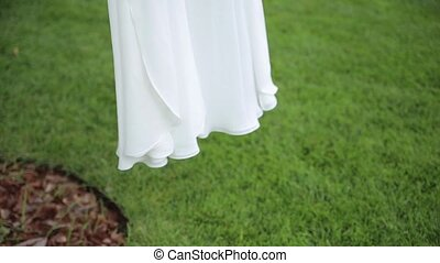 White wedding dress hangs on clothes for hanger. Close up -...