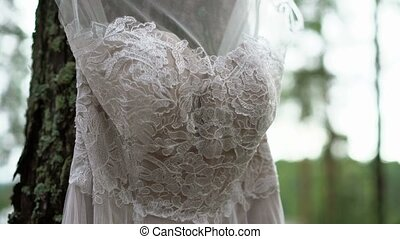 White wedding dress in forest