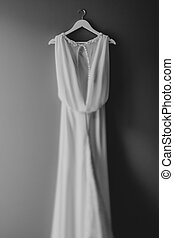 White wedding dress of the bride with a cutout on the back on a hanger on a nail with a shallow depth of field.