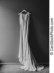 White wedding dress of the bride with a train on a hanger on a nail on a gray wall.