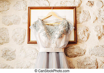 White wedding dress of the bride with patterns on a hanger on the picture frame.