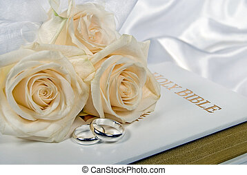 White Wedding - Roses and silver rings on white Bible.