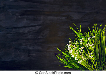 White wildflowers on a black wooden or metal background
