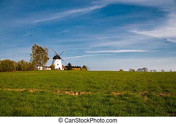 white windmill on the green farm field