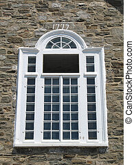 white window and stone wall