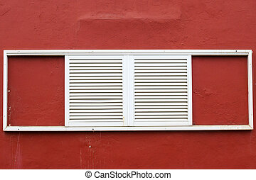 white window shutters on a red house wall