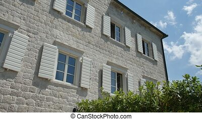 White window shutters. The facade houses in Montenegro -...