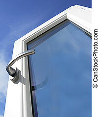 White window with silver handle with blue sky in the...