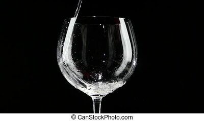 White wine being poured into a glass of black background. Slow motion.