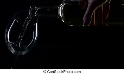 White wine being poured into a wine glass, silhouette, black...