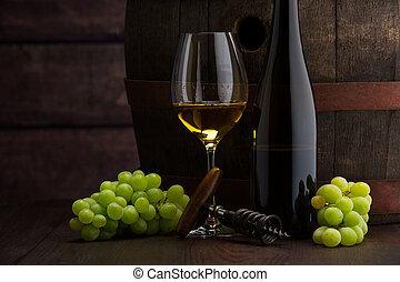 white wine bottle and wine glass on wodden barrel