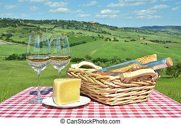 White wine, cheese and bread on the chequered cloth against Tusc