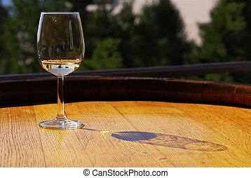 White Wine - Glass of white wine on a wooden barrel