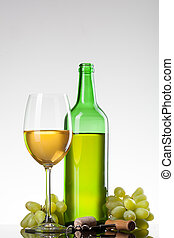 White wine in glass with grape and bottle