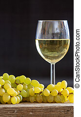 White wine in wineglass next to a bunch of grapes on a wooden table. Vertical portrait of alcohol drink and fruit on black background.