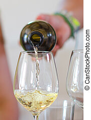 White wine is pouring into wine glass