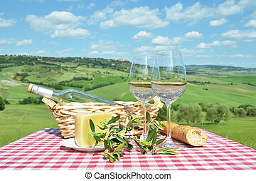 White wine on the table against Tuscan landsacpe, Italy