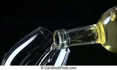 White wine poured into a wineglass, black, closeup, slowmotion